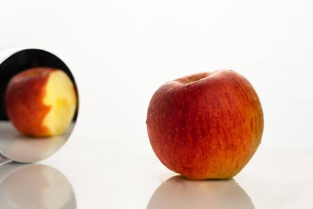 red orange yellow apple fruit for food in the mirror in paradox reality concept on white background