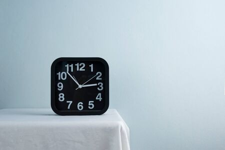 black and white modern clock at three pm on table in light blue interior cozy room background