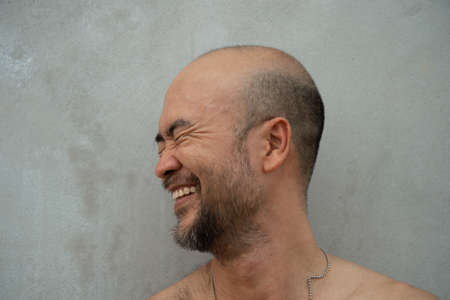 30-40s bald or skin head beard Japanese laughing happy man with grey loft cement background