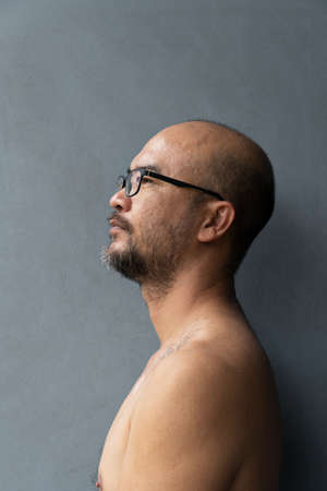 topless 40s beard bald Asia man with eyeglasess portrait on grey wall