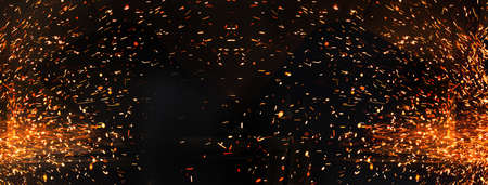 glowing glitter spark orange light fire on black industrial or party banner background