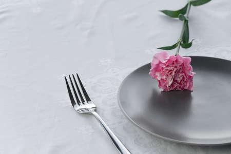 dark grey plate with natural pink carnation flower for food restaurant service background