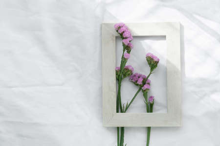 nature small purple flower in grey white wood frame on sunlight fabric background