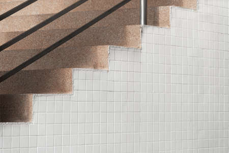 brown stone stair with white old small square tiles wall architecture background