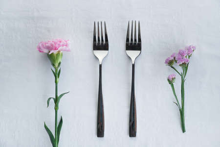 two identical silver fork with pink carnation and purple flower for food restaurant service background