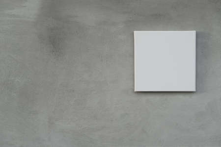 single empty white square canvas frame on grunge grey concrete wall background Imagens