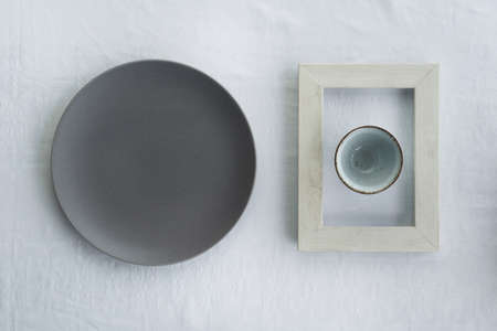 dark grey plate and tea ceramic cup for drink in wood frame minimalism food restaurant background