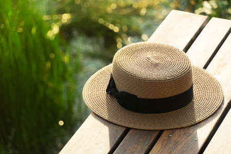 brown traveling woman hat on wood terrace with outdoor lake meadow view sunlight nature background Imagens