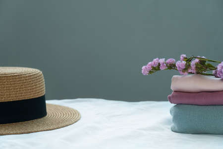 brown summer hat with stack of pink blue pastel cloth and purple natural flower cozy home interior background