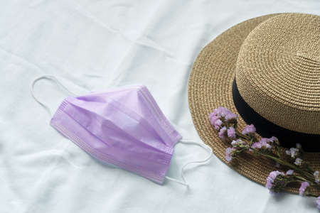 brown women travel summer hat with white purple corona virus protection health mask and spring flower on indoor white fabric background