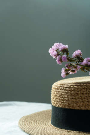sunlight summer brown hat with nature purple flower on blue grey background
