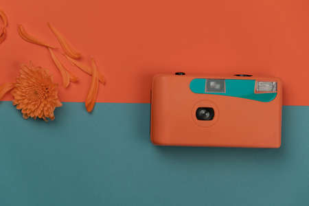 pastel blue orange plastic film camera and flower for summer traveling or vacation background