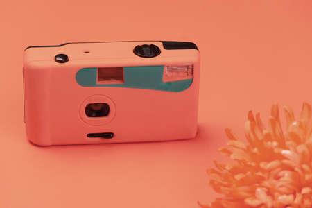 pastel orange pink blue plastic camera with blur flower vintage background