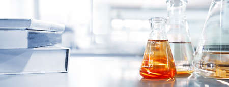 glass flask with orange solution and white text book in chemistry laboratory school education banner background