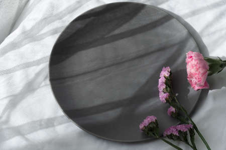 nature pink purple flower on dark grey ceramic dish in morning sunlight on white fabric for food background
