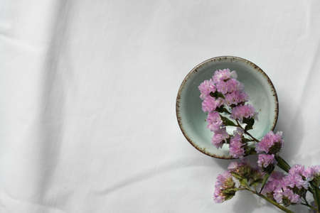 small purple flower with ceramic tea for drink on white background