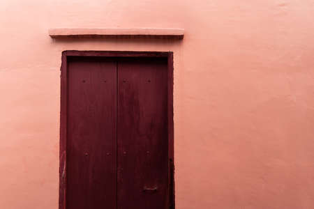 orange pink brown door with pink cement wall architecture background