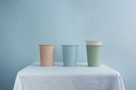 pastel green blue pink disposable plastic cup for take a way hot coffee drink on white table with blue wall background