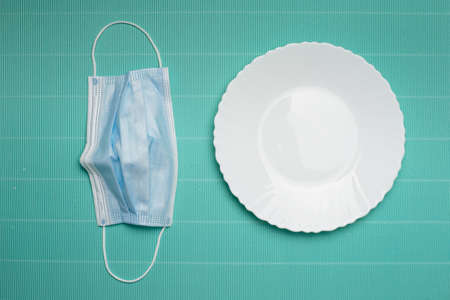 blue protection face mask for corona virus or covid 19 prevention on white food dish in restaurant on green paper background