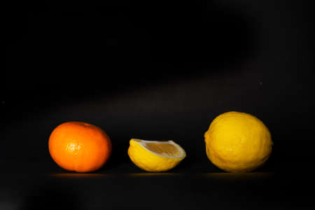 nature fresh slice yellow lemon and orange tangerine fruit for food on black background