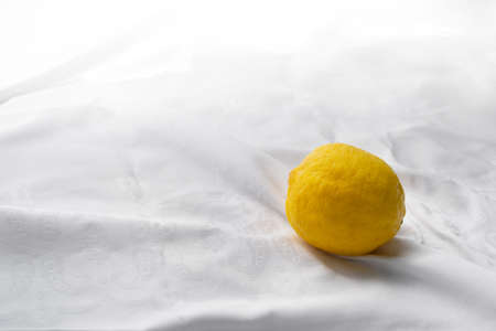 colorful single fresh yellow lemon fruit for food on white fabric background