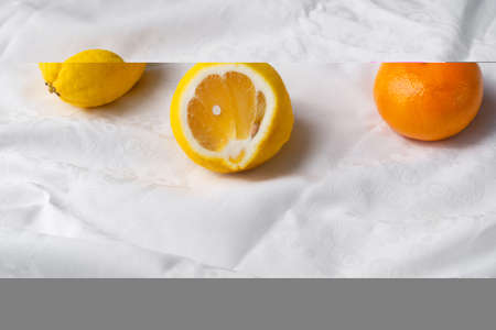 colorful fresh slice yellow lemon and orange tangerine fruit for food on white fabric background Imagens