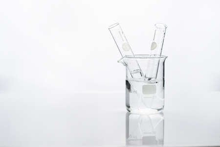 test tube in glass beaker with water in white chemistry science laboratory background