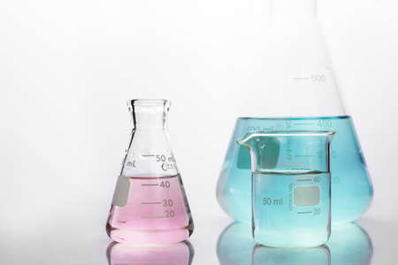 pink and blue solution in beaker and flask in white chemistry science laboratory background Imagens