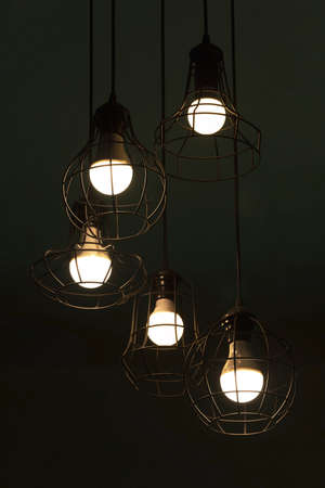 hanging classic black metal light bulb in night time interior on dark green background Imagens