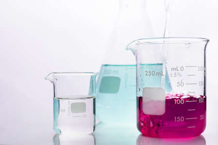 pouring water in beaker with pink chemical solution and  flask in white science laboratory background
