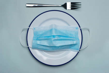 Blue protection face mask for coronavirus or covid 19 health prevention on white food dish and silver fork in restaurant