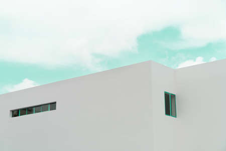 white concrete minimalism architecture building with cloud green blue sky background