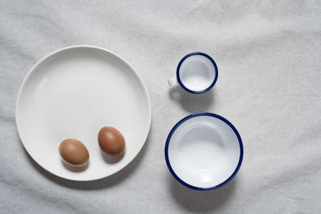 top view of two egg in white dish bowl and cup for food in drink on cotton fabric background