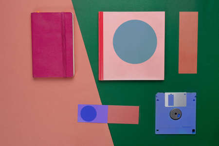 colorful pink red notebook paper and blue diskette in retro or vintage style business green orange background Imagens