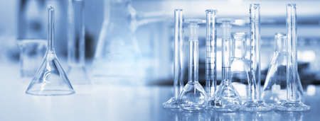 glass flask funnel and cylinder in soft blue light medical science laboratory banner background