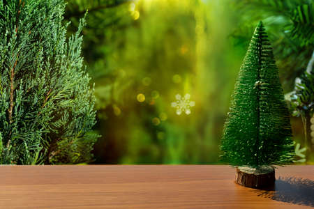 small Christmas tree and white snow on wood table and orange green pine nature