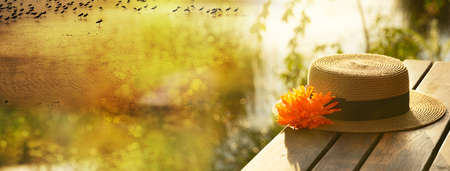 woman hat with orange flower on wood terrace in summer sunset at natural lake meadow water travel banner background Banque d'images