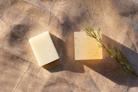two white and yellow organic natural product home made soap on golden fabric in health wellness concept Banque d'images