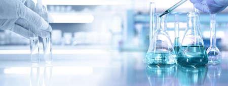 hand of scientist with test tube and flask in medical chemistry lab blue banner background