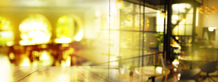 top of wood table blur orange sunlight in modern cafe interior banner background Banque d'images