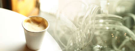 take away white paper cup of coffee on white desk with glass kettle background in cafe food and drink banner