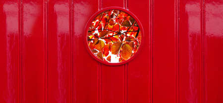 round or circle window with nature red autumn leave colorful wood wall architecture background Banque d'images
