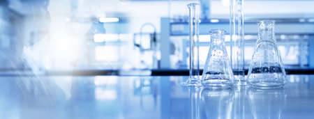 shadow of scientist and glass flask and cylinder equipment in medical science lab blue banner background