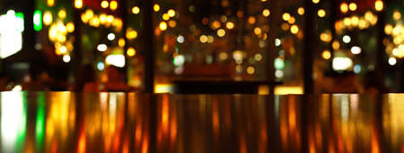 glowing reflection of party light on wood table in pub or bar in Christmas night banner background