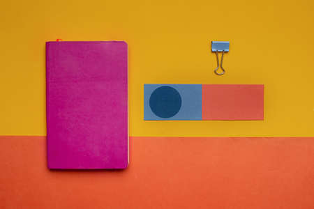 red pink notebook with colorful blue orange paper on yellow colorful background Imagens - 165376842