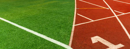 green artificial football field and red brown running tract sport filed banner background