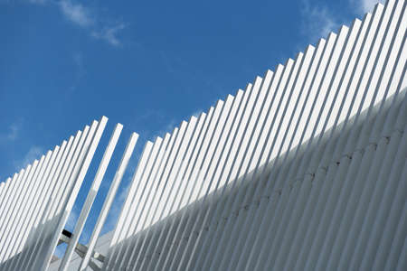 contemporary white grey metal industrial architecture on blue sky background