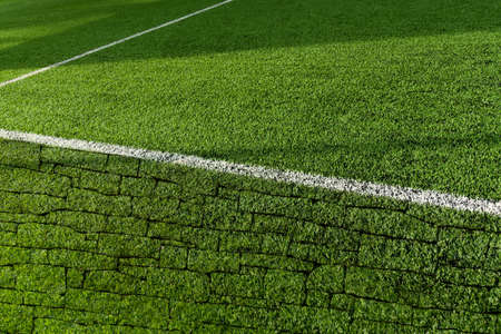 green artificial grass football or soccer field with white line and brick wall texture with sunlight background