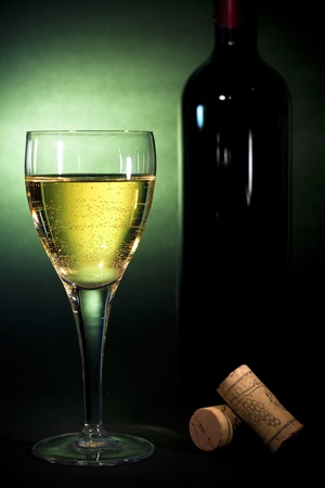 aligote: Crystal wine glass with white wine and a bottle, on black background with green gel, Luxury art background for beverages (part of collection)