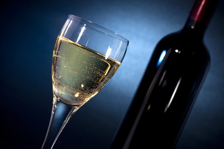 aligote: White wine on a glass closeup & a bottle, shoot on black background with blue gel Stock Photo
